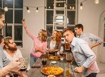 Le groupe d'amis appréciant égalisant boit avec de la bière Images libres de droits