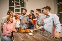 Le groupe d'amis appréciant égalisant boit avec de la bière Images stock