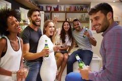 Le groupe d'amis appréciant des boissons font la fête à la maison Photo stock