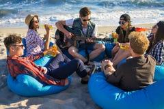 Le groupe d'amis avec la guitare et l'alcool sur la plage font la fête Photographie stock libre de droits