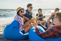 Le groupe d'amis avec la guitare et l'alcool sur la plage font la fête Image libre de droits