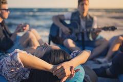 Le groupe d'amis avec la guitare et l'alcool sur la plage font la fête Images libres de droits
