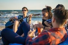 Le groupe d'amis avec la guitare et l'alcool sur la plage font la fête Images stock