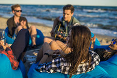 Le groupe d'amis avec la guitare et l'alcool sur la plage font la fête Photographie stock