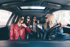 Le groupe d'amis ayant l'amusement affûtent la commande la voiture Chant et rire sur la route Image stock