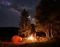 Le groupe d'amis chauffent leurs mains autour du feu de camp en bois près de la tente sous un ciel exceptionnellement étoilé Images stock