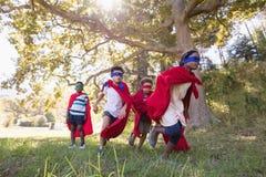 Le groupe d'amis dans le super héros costume le fonctionnement au terrain de camping Image libre de droits