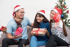Le groupe d'amis de l'Asie s'asseyant sur le sofa célèbrent Noël et le Ne Photo libre de droits