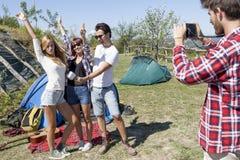 Le groupe d'amis des vacances prend des photos au terrain de camping Photo stock