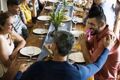 Le groupe d'amis divers dînent ensemble Image stock