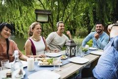 Le groupe d'amis divers dînent ensemble Images stock
