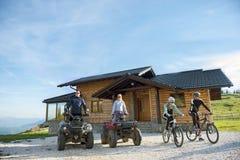 Le groupe d'amis est sur le point de commencer l'aventure sur des vélos de montagne et des vélos de quadruple d'atv devant la mai Image libre de droits