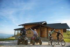 Le groupe d'amis est sur le point de commencer l'aventure sur des vélos de montagne et des vélos de quadruple d'atv devant la mai Images stock