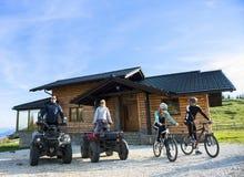 Le groupe d'amis est sur le point de commencer l'aventure sur des vélos de montagne et des vélos de quadruple d'atv devant la mai Photos libres de droits