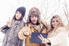 Le groupe d'amis fait à connexion de victoire la neige Photographie stock