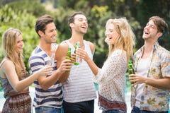 Le groupe d'amis grillant des bouteilles à bière s'approchent de la piscine Photo libre de droits