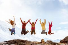 Le groupe d'amis heureux saute contre des montagnes photo libre de droits