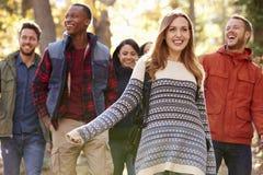 Le groupe d'amis heureux trimardant ensemble dans une forêt, se ferment  Photographie stock