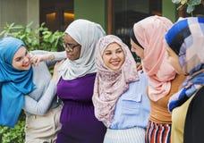 Le groupe d'amis islamiques arme autour et souriant ensemble Image stock