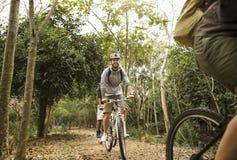 Le groupe d'amis montent le vélo de montagne dans la forêt ensemble Images stock