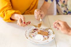 Le groupe d'amis remettent la fourchette de participation découpant en tranches en gâteau à la carotte avec le glaçage images libres de droits