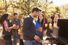 Le groupe d'amis s'élèvent à un barbecue, un faisant cuire au gril Image libre de droits