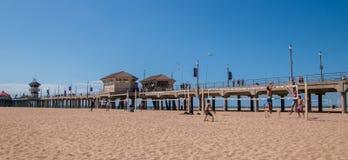 Le groupe d'amis sont vus jouer au volleyball à côté du pilier de Huntington Beach photo stock