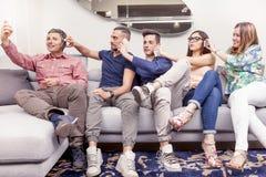 Le groupe d'amis sur le divan prend un selfie d'une manière drôle Photos stock