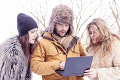 Le groupe d'amis voient un ordinateur portable dans la neige Photo libre de droits