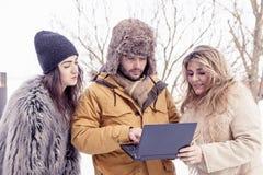 Le groupe d'amis voient un ordinateur portable dans la neige Photographie stock