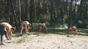 Le groupe d'athlètes réchauffant son corps et de mains avant la formation chez les jeunes hommes musculaires forts de forêt s'éte photos stock