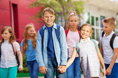 Le groupe d'enfants avec des sacs à dos s'approchent du bâtiment scolaire Image libre de droits