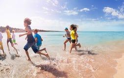 Le groupe d'enfants courent loin sur la plage sablonneuse Photos stock