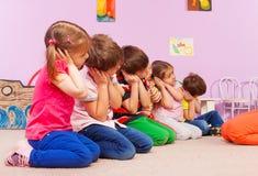 Le groupe d'enfants dans le jardin d'enfants feignent pour dormir Photographie stock