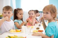 Le groupe d'enfants de jardin d'enfants prennent le déjeuner photographie stock