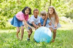 Le groupe d'enfants joue avec le globe du monde dans le jardin Images stock
