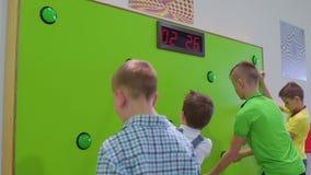 Le groupe d'enfants jouent un jeu de vitesse de réaction dans le musée scientifique