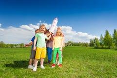 Le groupe d'enfants se tiennent en cercle avec la fusée de carton Photographie stock libre de droits
