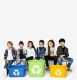 Le groupe d'enfants tenant des déchets avec réutilisent le symbole sur Blackgr blanc Photos stock