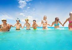 Le groupe d'enfants tenant des mains marchent dans l'eau de mer Photos stock