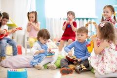 Le groupe d'enfants vieillissent 3-4 ans jouant les jouets musicaux divers Première éducation musicale dans le jardin d'enfants images stock