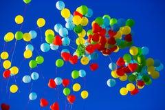 Le groupe d'hélium multicolore a rempli ballons dans le ciel Photographie stock libre de droits