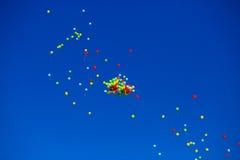 Le groupe d'hélium multicolore a rempli ballons dans le ciel Photos libres de droits