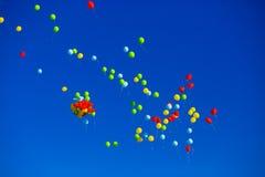 Le groupe d'hélium multicolore a rempli ballons dans le ciel Image stock