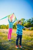 Le groupe d'heureux et de sourire badine le playingin avec le cerf-volant extérieur Photo stock