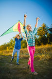 Le groupe d'heureux et de sourire badine le playingin avec le cerf-volant extérieur Images libres de droits