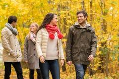 Le groupe d'hommes de sourire et les femmes en automne se garent Image libre de droits