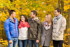 Le groupe d'hommes de sourire et les femmes en automne se garent Photos stock