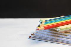 Le groupe d'objets se ferment vers le haut du concept de nouveau au fond de tableau noir de noir de carnet de crayon de couleur d Photos stock