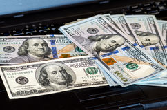 Le groupe de billets d'un dollar jetés sur un clavier d'ordinateur portable a comporté le bokeh defocused Images stock